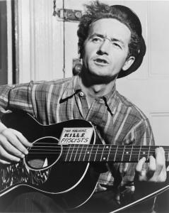 Woodie Guthrie con la sua chitarra acustica e l'immancabile adesivo